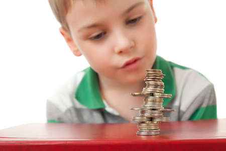 boy in striped T-shirt  looking at curve pile from coins coins  isolated on white background photo