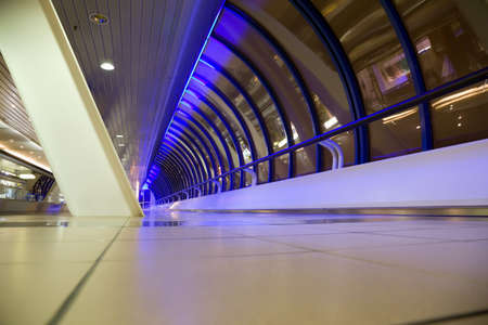 Long corridor with big windows in modern building at night, foreshortening from below, wide angle