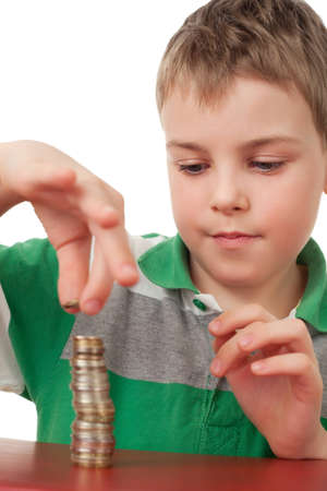 boys only: boy in striped T-shirt  stacking up coins  isolated on white background