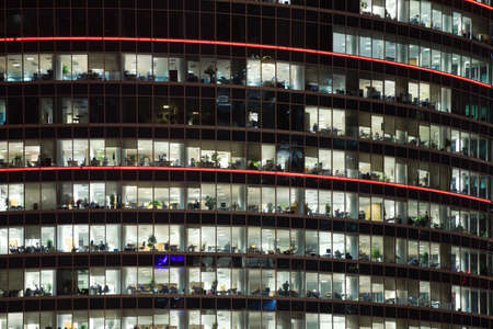 office equipment: modern office building with big windows at night, in windows light shines  Editorial