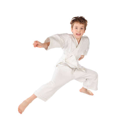 karateka: karateka boy in white kimono jumping isolated on white background