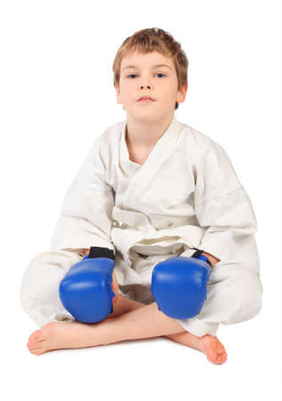 little boxer boy in white dress and blue boxing gloves sitting isolated on white photo