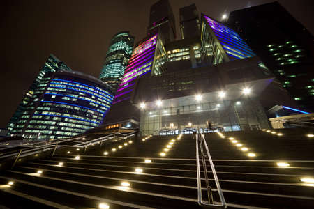 Facade of modern office building at night, skyscraper in moscow, foreshortening from below, steps leaders to grand entrance
