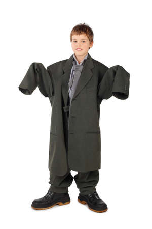 oversized: little boy in big grey mans suit and boots stabding isolated on white background Stock Photo