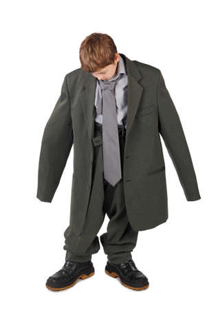 oversized: little boy in big grey mans suit and boots looking at floor isolated on white background