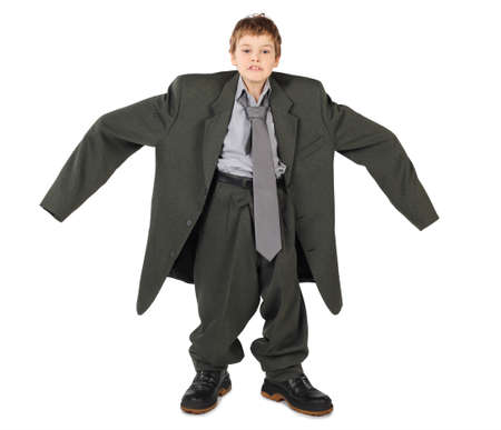 oversized: little boy in big grey mans suit and boots nads at sides isolated on white background