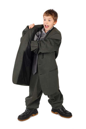 oversized: little boy in big grey mans suit and boots hand in pocket isolated on white background Stock Photo