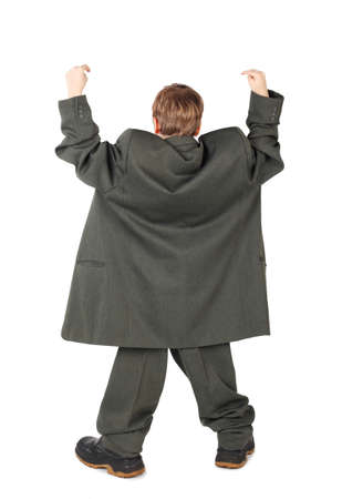 oversized: little boy in big grey mans suit and boots hand view from back isolated on white background Stock Photo