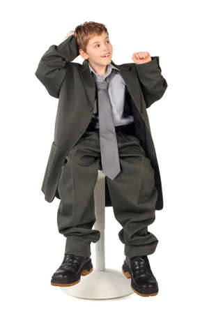 little boy in big grey mans suit sitting on chair isolated on white background photo
