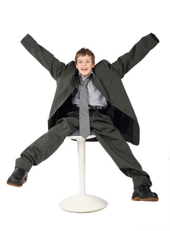 oversized: little boy in big grey mans suit sitting on chair and smiling isolated on white background