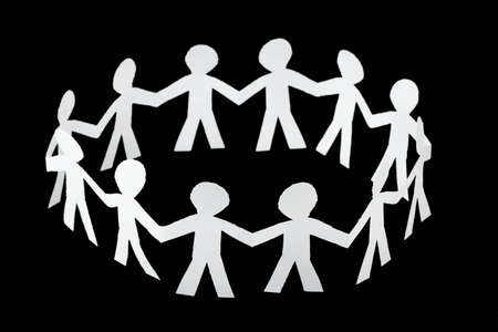 paper little people cutouts dance in ring isolated on black background Stock Photo - 12479179