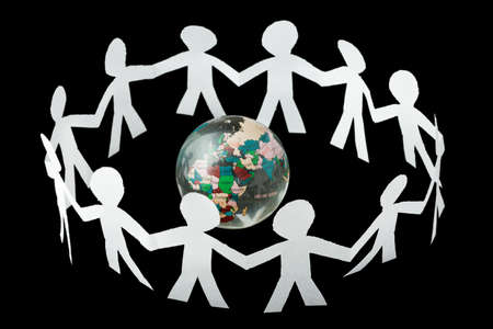 social gathering: paper little people cutouts sing and dance in ring around small globe isolated on black background