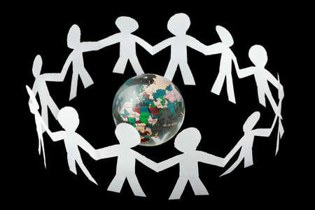 apoyo social: recortes de papel pequeña gente cantan y bailan en círculo alrededor de mundo pequeño aislado sobre fondo negro Foto de archivo
