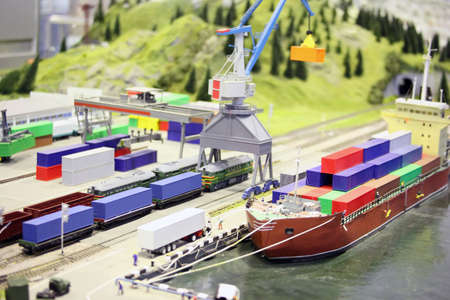 waggon: model of railroad station and sea port. ship, railroad, train, buildings and other constructions. focus on a second waggon of train.