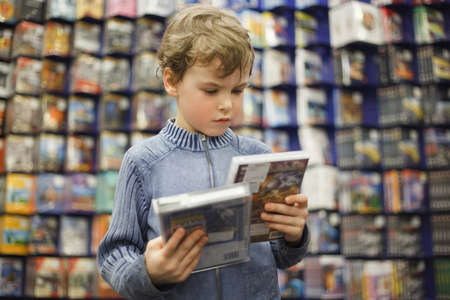 young boy chooses one of two dvd in special store, ready contents photo