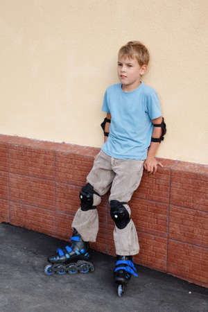 Boy in rollerskates, knee and elbow pads standing near wall.