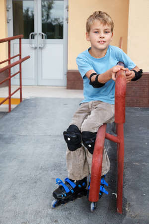 elbow pads: Boy in rollerskates, knee and elbow pads, sitting on the railing in front of house.