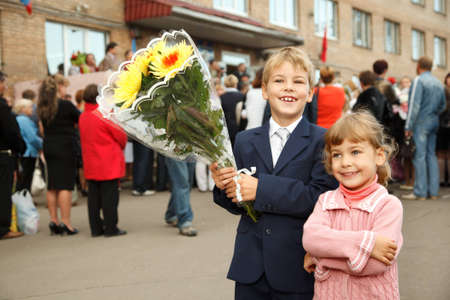 day of school: First class, brother and sister with  bouquet of flowers, standing at  entrance to school.
