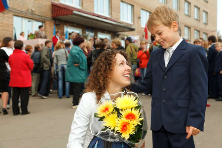 life event: First class, a boy and his mother a bouquet of flowers stood at the entrance to the school.