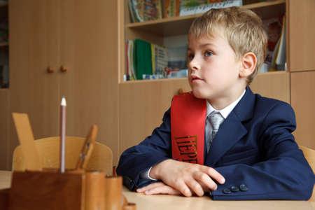 elementary age boys: First class. Boy in school uniform at his desk.