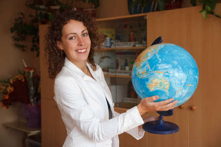 Portrait of schoolteacher in a white blouse in school. Smiling, holding globe. photo