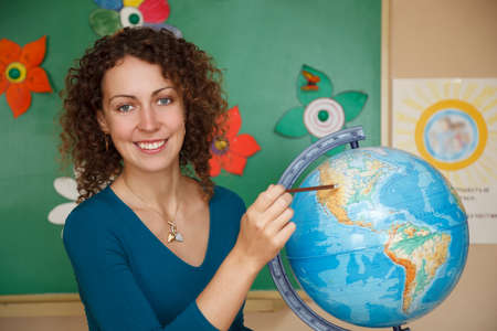 human geography: Portrait of schoolteacher in a white blouse in school. Smiling, looking into camera showing pencil on globe. Stock Photo
