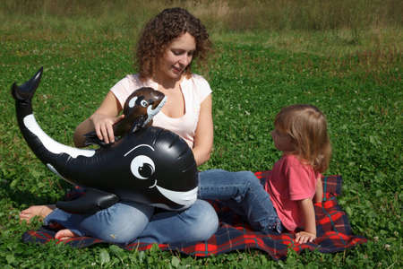 Mom and daughter play on grass on sunny day with inflatable toys. photo