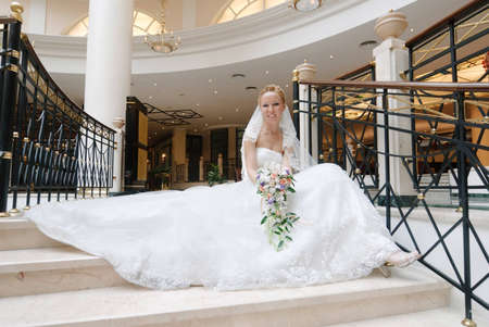 Bride in beautiful wedding dress sits on wide spiral staircase with bunch of flowers in hands. Stock Photo - 12734201