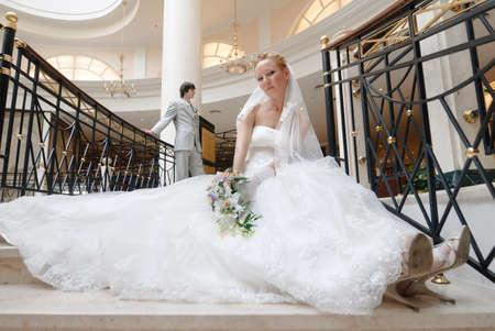Bride in beautiful wedding dress sits on wide spiral staircase with bunch of flowers in hands. On background there is groom.