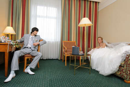 Bride and groom in hotel room looking at each other.