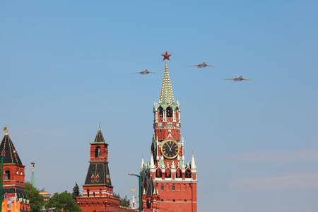 MOSCOW - MAY 9: Supersonic, variable-sweep wing heavy strategic Tu-160 airplanes fly over Red Square, Spasskaya Tower on victory parade on May 9, 2010 in Moscow, Russia Stock Photo - 12512212
