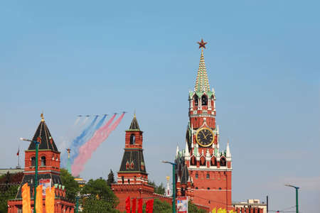 may 9: MOSCOW - MAY 9: Airplanes make color contrail of russian flag colors and fly over Red Square, Spasskaya Tower on parade in honor of Great Patriotic War victory on May 9, 2010 in Moscow, Russia