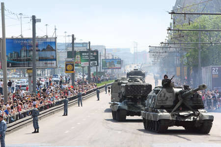 weaponry: MOSCOW - MAY 9: People looks on weaponry and tank on road on parade in honor of Great Patriotic War victory on May 9, 2010 in Moscow, Russia. 160 military vehicle took part in parade