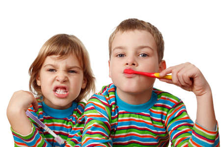 Brother and sister in same shirts brush their teeth on white background. Close-up. Isolated.