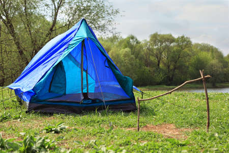 mere: Blue deployed tent stands on river bank in green forest on summer day