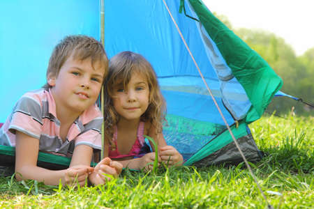Little brother and sister lying inside blue tent on green grass on summer day and looking forward
