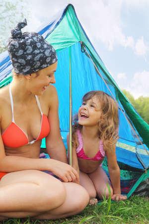traje de bano: Feliz madre y su peque�a hija se sienta cerca de la tienda azul en la hierba verde