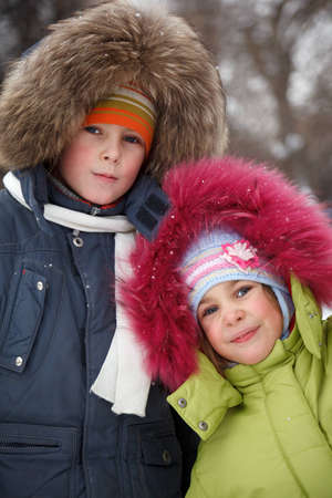 fur hood: Brother and sister smiling looking into camera in winter forest, in jackets with fur hoods on their heads.