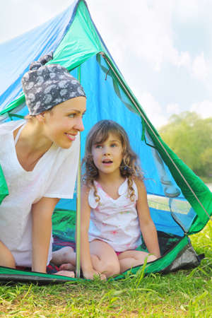Happy mother and her little daughter in white clothes sitting near blue tent on green grass Stock Photo - 12635962