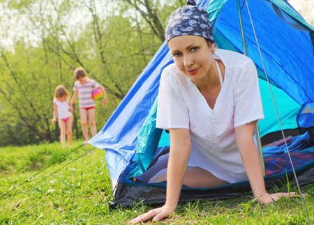 Happy young woman sits inside blue tent on green lawn inside forest, her kids game on lawn, mother on focus photo