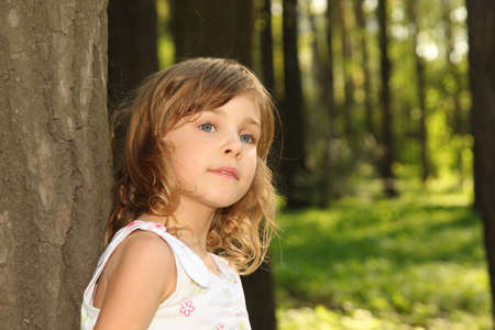 Little cute girl with curly blonde hair in white clothes leaning against a tree inside green forest at sunny day Stock Photo - 12635941