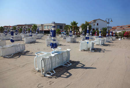 many white striped deck chairs and beach umbrellas are on empty beach.