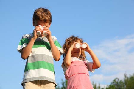 yogur: La niña y el niño, en contra de la obra el cielo azul con pequeñas botellas de yogur, que representa el binocular. Foto de archivo