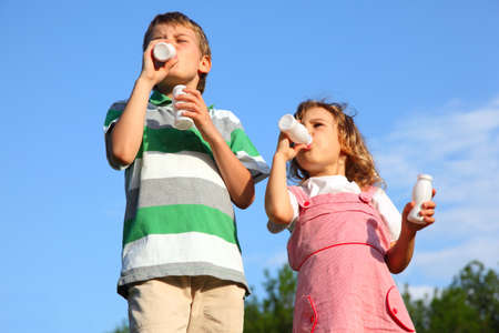 Little boy and the girl against the blue sky, with pleasure drink yoghurt. photo