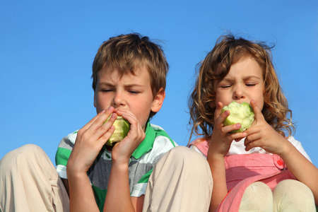 Two beautiful children, against the blue sky eat the big green apples. photo