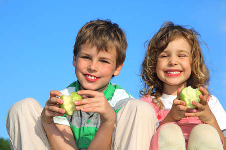 sister: The girl and the boy have a rest on the nature, smile and eat apples.