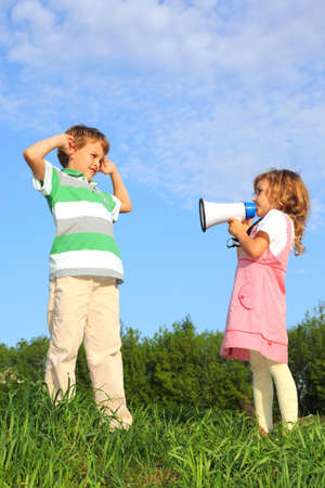 Children have fun on the nature, and play with a loudspeaker.