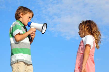 berisping: De kleine jongen, op de natuur, doet berisping tot het meisje door een luidspreker.