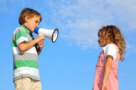 reprimand: The little boy, on the nature, does reprimand to the girl through a loudspeaker.