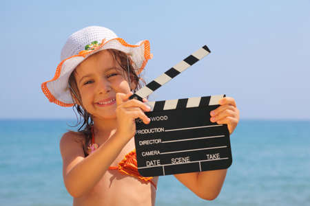 clap: beautiful little girl standing on beach and holding clapboard. focus on girl eyes